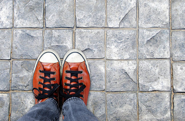 Feet in leather sneaker on pavement background