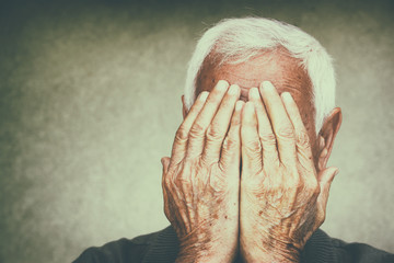 portrait of senior man covering his face with his hands. retro f