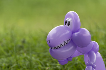 Closeup of purple balloon animal dinosaur in green grass of back