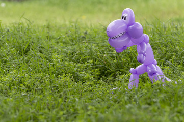 Purple balloon animal dinosaur in green grass of back yard