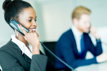 A beautiful, black, young woman working in a call center in an o