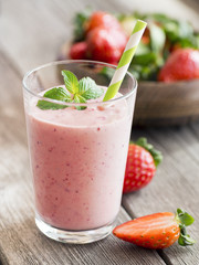 Strawberry smoothie in a glass with mint on wooden background