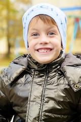 Four year boy in Autumn park wearing a warm hat