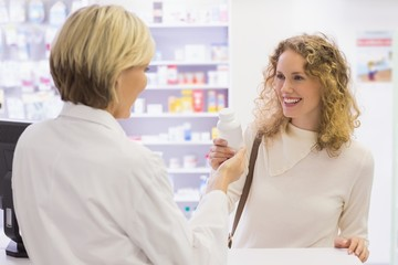 Smiling pharmacist and customer discussing a product