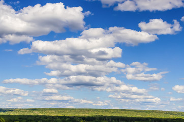 Beautiful blue sky with fluffy clouds and green forest
