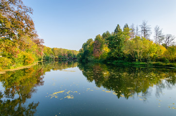 Attractive autumn landscape with beautiful reflection of woods f