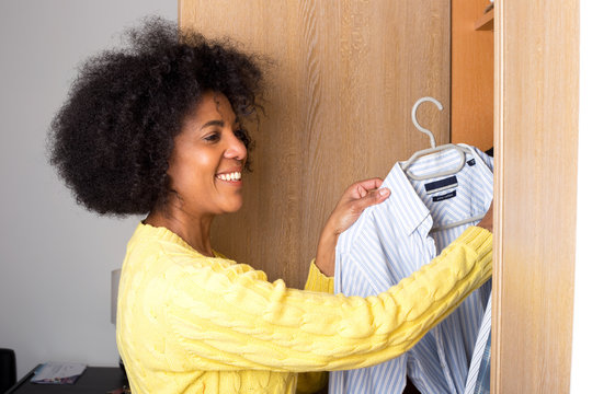 a young woman at home taking a shirt out of a wardrobe
