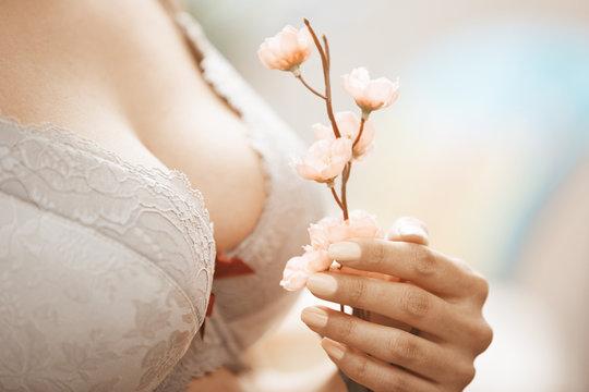 Woman in brassiere holding Sakura flower