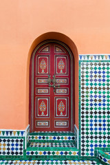 Moroccan painted door red designs against orange wall with tile