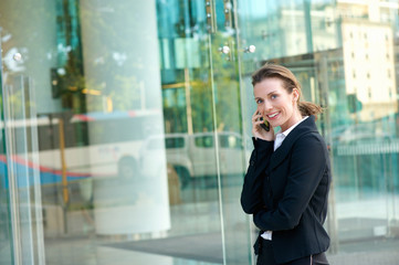 Happy business woman walking and calling by mobile phone