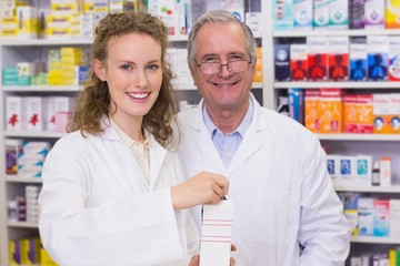 Pharmacists holding medicine looking at camera