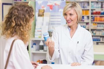 Pharmacist showing medicine jar to costumer