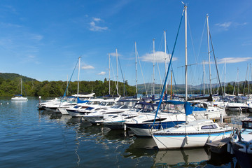 Sailing boats and yachts with masts row on lake