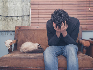 Sad and depressed young man with cat on sofa