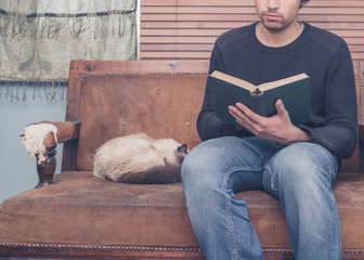 Young man sitting on sofa with cat is reading