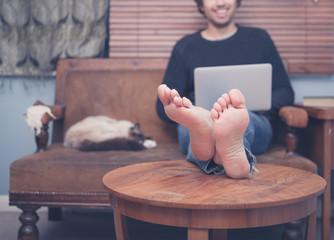 Barefoot man working on laptop