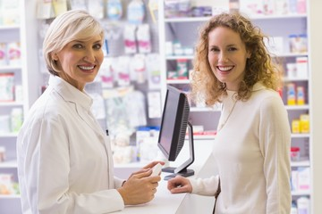 Pharmacist and costumer smiling at camera