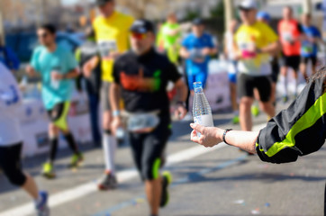 Marathon running race, runners on road, volunteer giving water