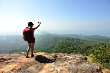 woman hiker taking photo at mountain peak cliff