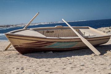 Wooden boat with two oars on beach