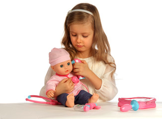 girl playing nurse with her baby-doll