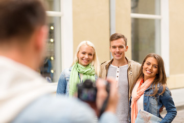 group of smiling friends taking photo outdoors