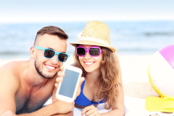 Happy couple showing smartphone at the beach