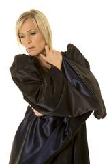 woman in black cloak hand by neck look side
