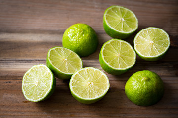 Fresh cut limes on wooden background