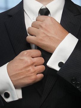 man in a black suit straightens his tie