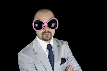 businessman wearing big funky pink glasses isolated on black bac