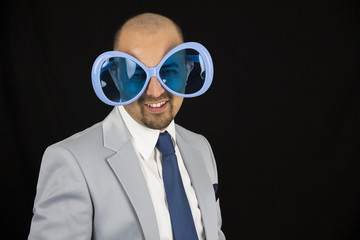 businessman wearing big funky blue glasses isolated on black bac
