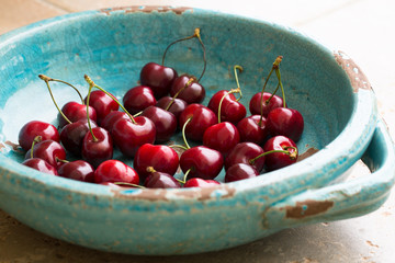Red cherries in antique bowl