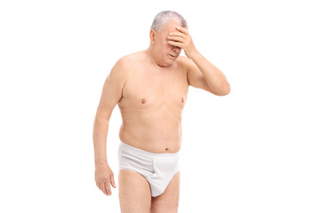 Upset senior man in underwear gesturing with his hand