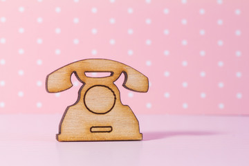 Wooden icon of telephone on pink background