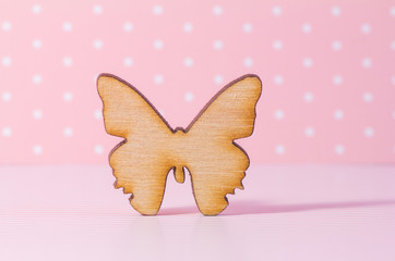 Wooden icon of butterfly on pink background