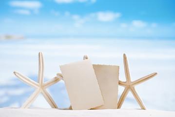 white starfish with blank retro photo on white sand beach, sky a