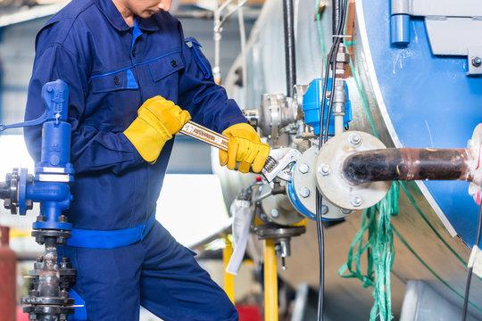 Mechanic repairing machine in industrial plant