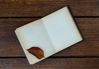 open blank old notebook on wooden table with dry leaves