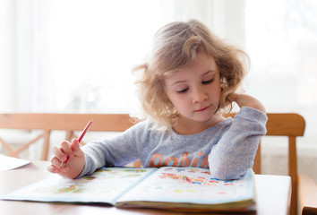 Little girl drawing with pencils and learning at home