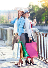 Two beautiful girls with shopping bags showing thumbs up