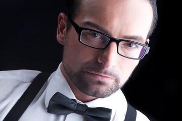 Junger sympathischer Geschäftsmann mit Brille blickt