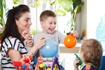 woman with two children playing with balloons in home interior