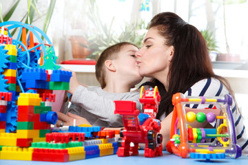 mother kissing her son sitting  in home interior