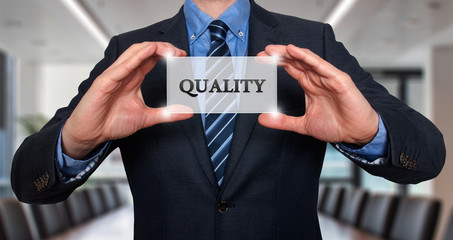 Businessman holding Quality sign.  Stock Photo
