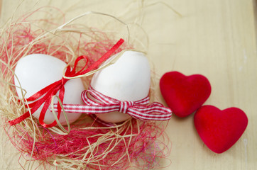 Two white eggs in a nest and two hearts