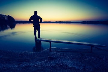 Lake sunset landscape with man silhouette