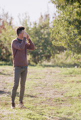 An apple orchard in Utah. Man taking a picture.