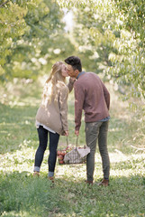 An apple orchard in Utah. Couple carrying a basket of apples, kissing.