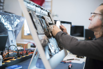 Computer Repair Shop. A man with a computer monitor, taking it apart to mend it.